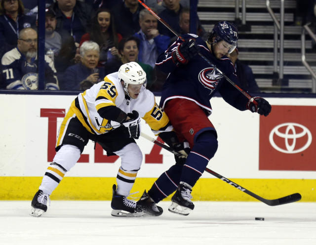 Pittsburgh Penguins forward Jake Guentzel, left, reaches for the puck against Columbus Blue Jackets forward Josh Anderson during the second period of an NHL hockey game in Columbus, Ohio, Saturday, March 9, 2019. (AP Photo/Paul Vernon)