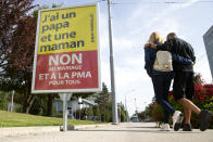 A couple walk past a poster showing a slogan in Perly near Geneva, Saturday Sept. 25, 2021. Voters in Switzerland will decide Sunday whether to allow same-sex marriages in the rich Alpine country, one of the few in Western Europe where gay and lesbian couples do not already have the right to wed. Opponents have argued that replacing civil partnerships with full marriage rights somehow would undermine families based on a union between one man and one woman. (Salvatore Di Nolfi/Keystone via AP)