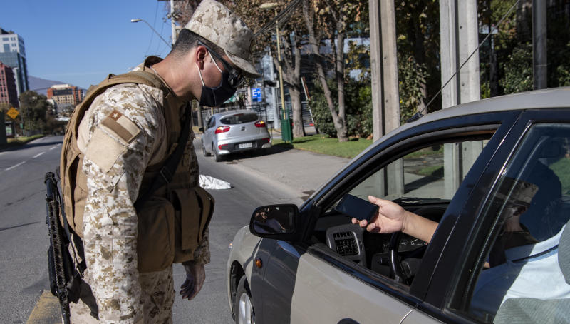 A soldier stops a car at a checkpoint in Santiago, on May 16, 2020, amid mandatory total quarantine due to the new coronavirus pandemic. - Chile's government ordered a mandatory total quarantine for the capital on Wednesday after a 60 percent spike in coronavirus infections in the previous 24 hours. (Photo by Martin BERNETTI / AFP) (Photo by MARTIN BERNETTI/AFP via Getty Images)