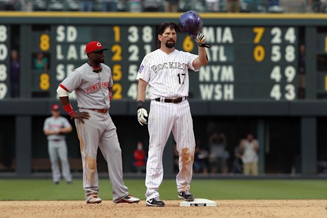Colorado Rockies' Todd Helton, front, tips his helmet to the crowd as Cincinnati Reds second baseman Brandon Phillips looks on after Helton doubled in the seventh inning for his 2,500th career hit in the Rockies' 7-3 victory in a baseball game in Denver on Sunday, Sept. 1, 2013. (AP Photo/David Zalubowski)