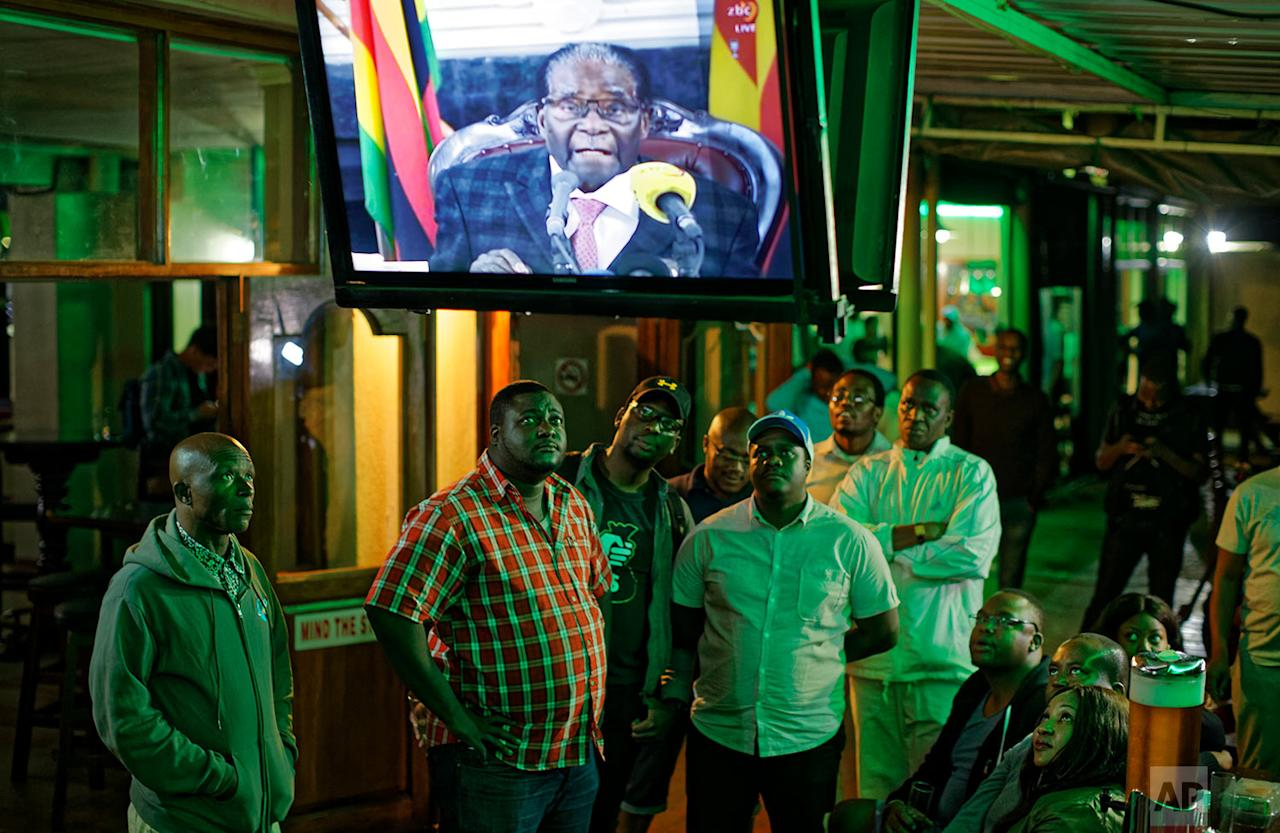 <p>Zimbabweans watch a televised address to the nation by President Robert Mugabe at a bar in downtown Harare, Zimbabwe. President Robert Mugabe has baffled the country by ending his address on national television without announcing his resignation. (AP Photo/Ben Curtis) </p>