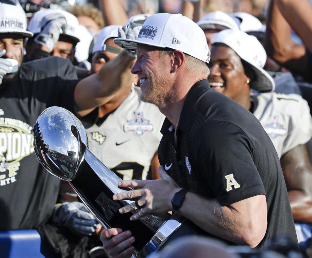 Central Florida head coach Scott Frost holds the winning trophy after defeating Memphis in the American Athletic Conference championship. (AP Photo/John Raoux)