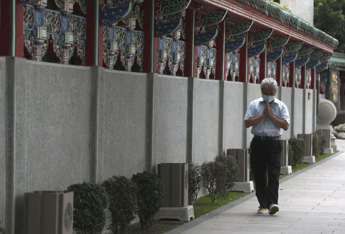 A Taiwanese man prays and detours outside of Longshan Temple after the COVID-19 alert raise to level 3 in Taipei, Taiwan, Tuesday, May 18, 2021. (AP Photo/Chiang Ying-ying)
