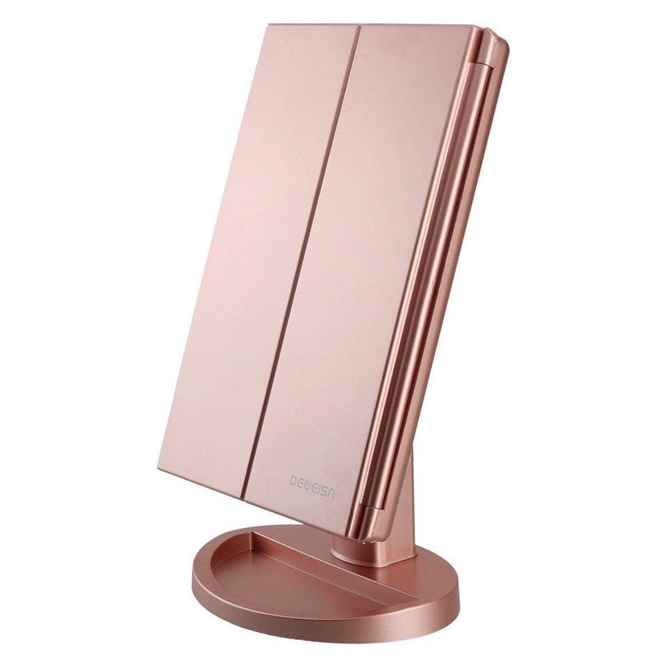 """<h3>Tri-Fold Lighted Vanity Mirror</h3><br>Getting glam just for fun? Invest in this rose gold lighted mirror, which even has a built-in tray for stashing your most-used beauty products.<br><br><strong>deweisn</strong> Tri-Fold Lighted Vanity Mirror, $, available at <a href=""""https://amzn.to/3qeV0Io"""" rel=""""nofollow noopener"""" target=""""_blank"""" data-ylk=""""slk:Amazon"""" class=""""link rapid-noclick-resp"""">Amazon</a>"""