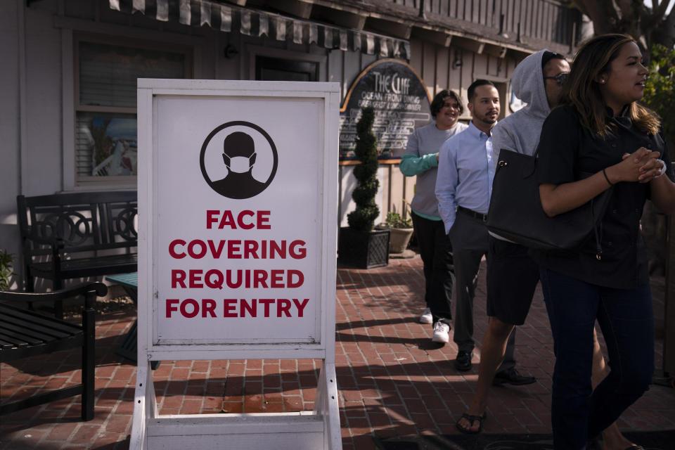 FILE - In this May 17, 2021, file photo, people walk past a sign requesting customers to wear masks in Laguna Beach, Calif. Federal health officials' new, more relaxed recommendations on masks have all but eclipsed another major change in guidance from the government: Fully vaccinated Americans can largely skip getting tested for the coronavirus. (AP Photo/Jae C. Hong, File)