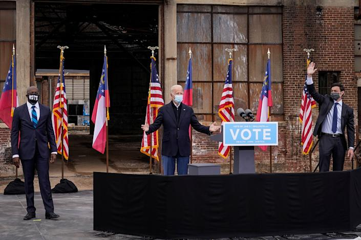 Flanked by U.S. Democratic Senate candidates Rev. Raphael Warnock (left) and Jon Ossoff (right), President-elect Joe Biden gestures to the crowd at the end of a drive-in rally at Pullman Yard on December 15, 2020 in Atlanta, Georgia. (Photo: Drew Angerer via Getty Images)