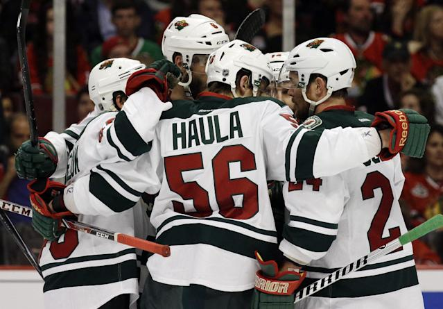 Minnesota Wild's Erik Haula (56) celebrates with teammates after scoring his goal against the Chicago Blackhawks during the first period in Game 5 of an NHL hockey second-round playoff series in Chicago,Sunday, May 11, 2014. (AP Photo/Nam Y. Huh)