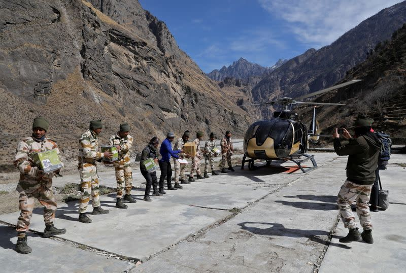 Members of Indo-Tibetan Border Police unload relief goods at a temporary base camp set up by ITBP for distribution of relief material in the affected areas, at Lata village