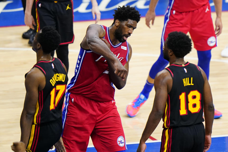 Philadelphia 76ers' Joel Embiid, center, reacts between Atlanta Hawks' Onyeka Okongwu, left, and Solomon Hill after being fouled during the first half of Game 1 of a second-round NBA basketball playoff series, Sunday, June 6, 2021, in Philadelphia. (AP Photo/Matt Slocum)
