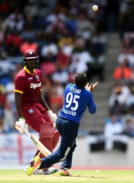 England's cricketer Adil Rashid (R) takes a catch to dismiss West Indies cricket team captain Jason Holder (back) during the second of the three-match One Day International series between England and West Indies on March 5, 2017