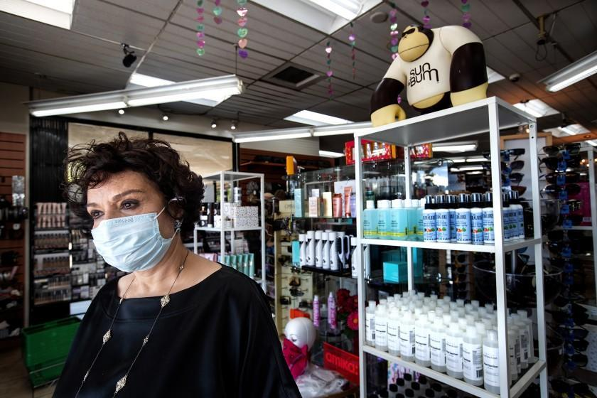 "SHERMAN OAKS, CA-MAY 15, 2020: Janet Tavakoli, 69, owner of Sherman Oaks Beauty Collection, wearing a protective mask against the coronavirus, is photographed next to bottles of hand sanitizer, right, for sale inside her store. The store is one of 60 non-essential businesses cited by Los Angeles City Attorney Mike Feuer for ""flouting the city's Safer at Home order. Tavakoli says she shut down her store for 2 weeks, losing $15,000 in sales but reopened after seeing beauty store competitors open. (Mel Melcon/Los Angeles Times)"