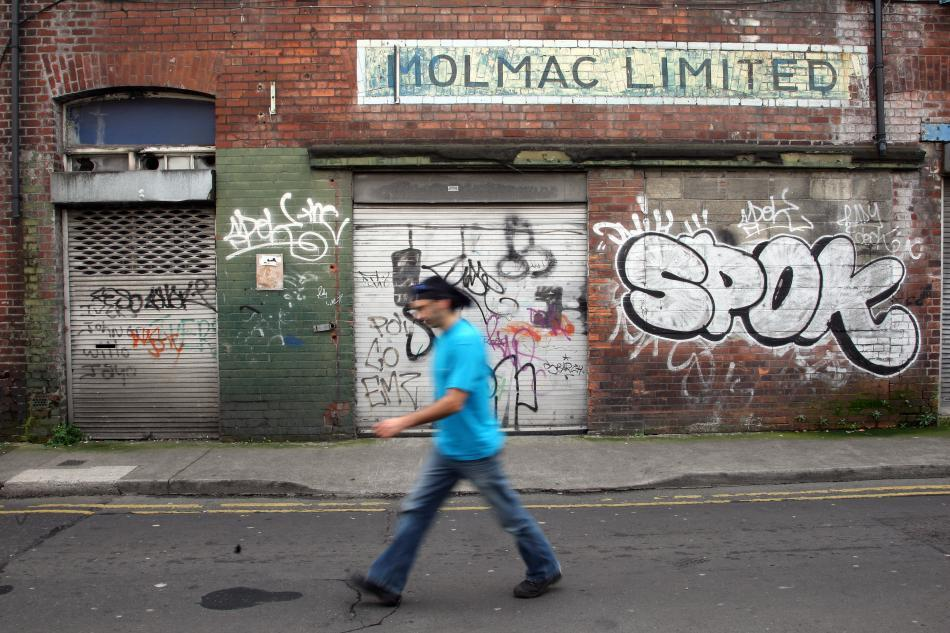 A man walks past graffiti in Dublin.