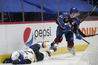 Colorado Avalanche left wing Gabriel Landeskog, right, picks up the puck as St. Louis Blues center Oskar Sundqvist loses his footing and slides against the boards during the second period of an NHL hockey game Wednesday, Jan. 13, 2021, in Denver. (AP Photo/David Zalubowski)