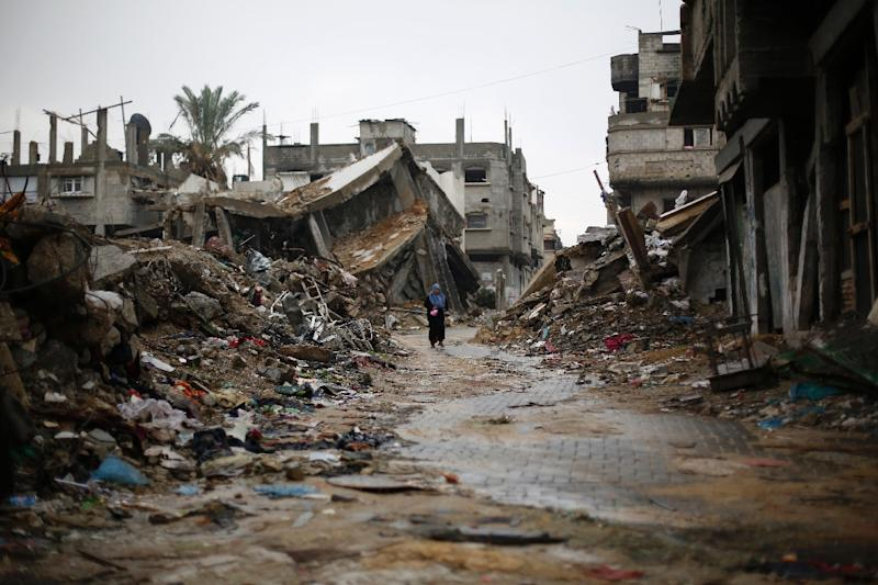 A Palestinian woman walks past houses that were destroyed during the 50-day Gaza war between Israel and Hamas-led militants, on November 24, 2014, in Gaza City