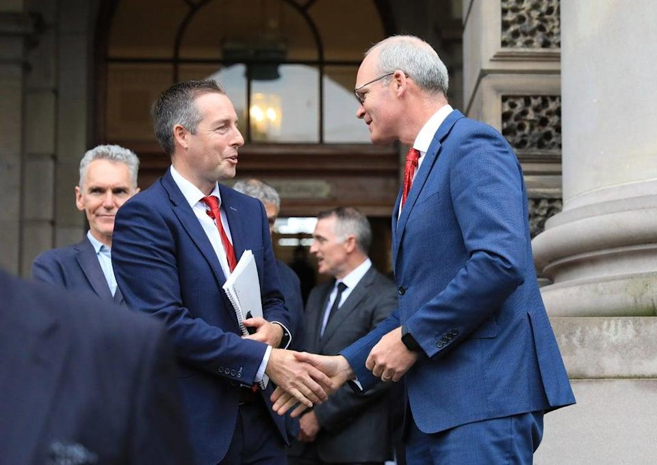 Northern Ireland First Minister Paul Givan (left) greets Ireland's Minister for Foreign Affairs Simon Coveney at a centenary event in Belfast (Peter Morrison/PA) (PA Wire)