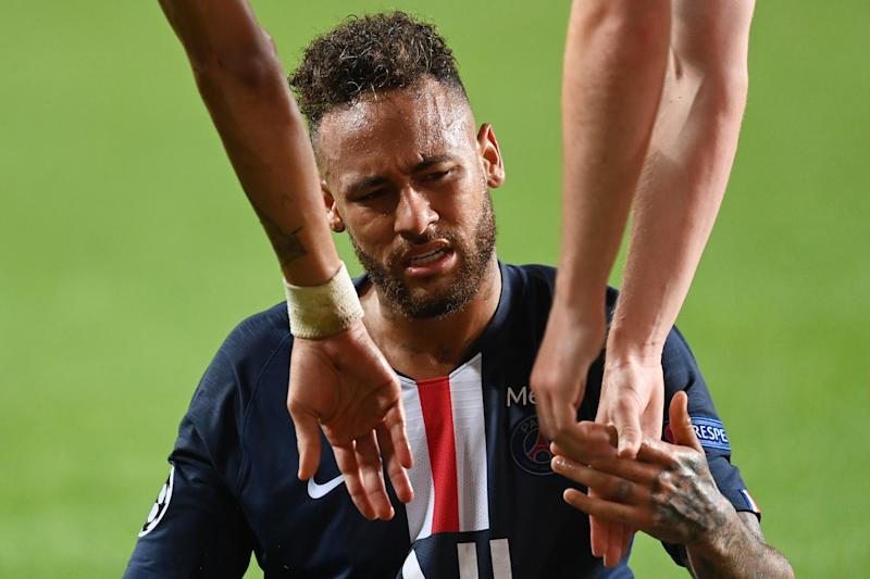 LISBON, PORTUGAL - AUGUST 18: Team mates of Neymar of Paris Saint-Germain reach out to help him up from the ground after going down during the UEFA Champions League Semi Final match between RB Leipzig and Paris Saint-Germain F.C at Estadio do Sport Lisboa e Benfica on August 18, 2020 in Lisbon, Portugal. (Photo by Michael Regan - UEFA/UEFA via Getty Images)