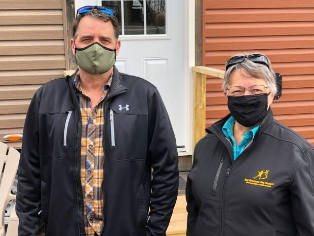 Carpenter Mike Roy, and Big Brothers, Big Sisters president of the board of directors Anita Legere standing outside of the tiny home.
