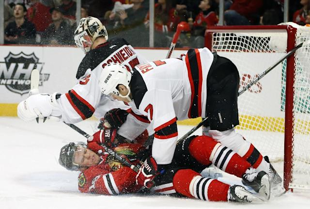 New Jersey Devils defenseman Mark Fayne (7) pushes Chicago Blackhawks center Jonathan Toews (19) to the ice next to goalie Cory Schneider during the second period of an NHL hockey game Monday, Dec. 23, 2013, in Chicago. (AP Photo/Charles Rex Arbogast)