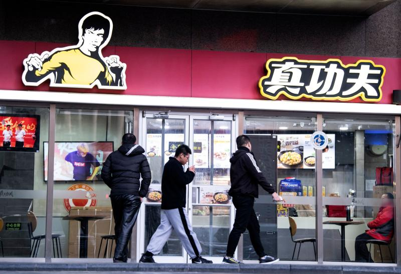People walk past the restaurant Real Kung Fu, or Zhen Gongfu in Mandarin, run by fast food chain Kungfu Catering Management, in Beijing on December 26, 2019. - Shannon Lee's Bruce Lee Enterprises is suing restaurant chain Kungfu Catering Management of having used her late father's image for 15 years in a logo without paying intellectual property rights. (Photo by Noel CELIS / AFP) (Photo by NOEL CELIS/AFP via Getty Images)