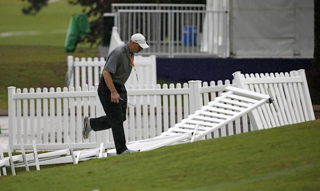 A man steps over fencing blown down around the practice green during a weather delay at the second round of the St. Jude Classic golf tournament Friday, June 6, 2014, in Memphis, Tenn. (AP Photo/Mark Humphrey)