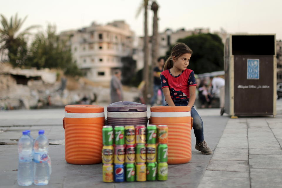 In this Saturday, July 27, 2019 photo, a girl sells cool drinks in the old city of Aleppo, Syria. Rebels still frequently strike with shelling and mortars into Aleppo, killing civilians nearly three years after the government recaptured the city. Aleppo is a symbol of how President Bashar Assad succeeded in turning the tide in Syria's long civil war with a series of wins, but it's equally a symbol of how he's been unable to secure a final victory. Half of Aleppo remains in ruins, and rebels remain on the doorstep. (AP Photo/Hassan Ammar)