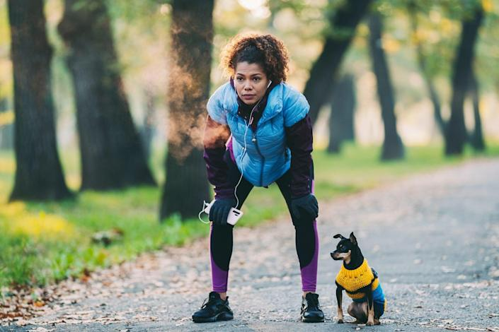 woman taking a breath after a run with her dog