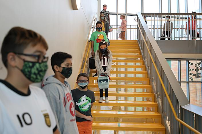Masked children line up at a safe social distance before heading into a lunchroom at Woodland Elementary School in Milford, Mass., on Sept. 11. (Suzanne Kreiter/Boston Globe via Getty Images)