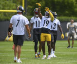 Pittsburgh Steelers wide receiver Juju Smith-Schuster mimics a basketball shot during the NFL football team's training camp in Pittsburgh on Friday, July 23, 2021. With him are quarterback Ben Roethlisberger (7), and wide receivers Chase Claypool (11) and James Washington (13). (Steve Mellon/Pittsburgh Post-Gazette via AP)