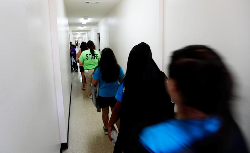Immigrants walk down the hall of a dormitory at the U.S. government's newest holding center for migrant children in Carrizo Springs, Texas, on July 9. (Photo: POOL New / Reuters)