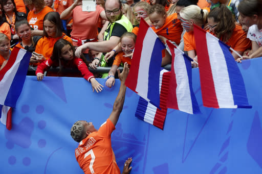 Netherlands' Shanice Van De Sanden, bottom, celebrates with supporters after the Women's World Cup Group E soccer match between the Netherlands and Cameroon at the Stade du Hainaut in Valenciennes, France, Saturday, June 15, 2019. The Netherlands defeated Cameroon by 3-1. (AP Photo/Michel Spingler)