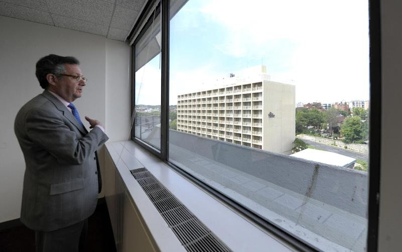 In this photo taken May 30, 2012, Penzance senior adviser Peter Greenwald looks out of a window from an office on the sixth floor of the Watergate Office Building in Washington. This particular office space is believed to be the former headquarters of the Democratic National Committee offices that were burglarized 40 years ago. The building out of the window is the former Howard Johnson's Hotel. Forty years ago police in Washington arrested five men breaking in to the Democratic National Committee offices in Washington. The name of the complex they were breaking into became infamous: the Watergate. These days, though, unless you know where to look, thereís little marking the location of the 1972 crime that ultimately led to the resignation of President Richard Nixon. The office building that was the site of the break in is still in use, though the tenants have changed. The adjacent hotel where the burglars stayed is currently closed. And another hotel across the street where a lookout waited with a walkie-talkie, monitoring the burglarsí progress, has been turned into a college dorm. (AP Photo/Susan Walsh)