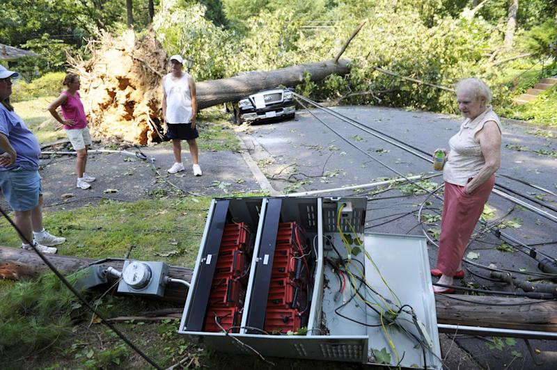 Marilyn Golias, right, looks at the remains of a utility pole which fell across the street from her house in Falls Church, Va., Saturday, June 30, 2012. Millions across the mid-Atlantic region sweltered Saturday in the aftermath of violent storms that pummeled the eastern U.S. with high winds and downed trees, killing at least 13 people and leaving 3 million without power during a triple-digit heat wave. (AP Photo/Cliff Owen)