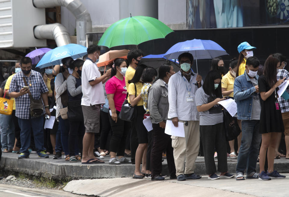 FILE - In this July 14, 2020, file photo, people line up for the coronavirus test in Rayong province, Thailand. The World Bank on Tuesday, Sept. 28, 2021, cut its economic growth forecast for developing countries in East Asia due to the impact of the coronavirus's delta variant and called on governments to help the poor and small businesses avoid long-term damage. (AP Photo/Sakchai Lalit, File)