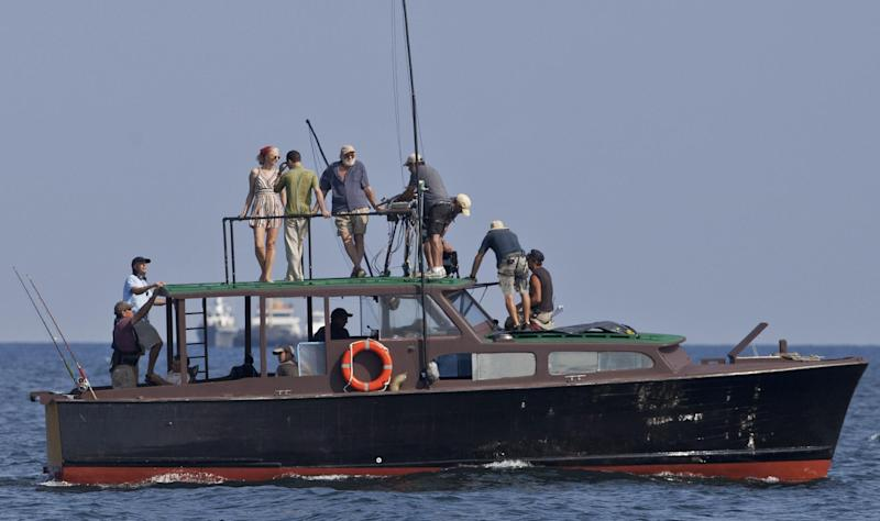 "In this April 24, 2014 photo, film director Bob Yari, left, with a black cap works with actors Joely Richardson, top left, Giovanni Ribisi, top second left, and Adrian Sparks, top thirt left, while shooting the movie ""Papa"" in the bay of Havana, Cuba. Though the title derives from the Nobel Prize-winning novelist's nickname, the movie is based on an autobiographical script by Denne Bart Petitclerc, who is played by Giovanni Ribisi, while Hemingway is portrayed by theater and screen veteran Adrian Sparks. (AP Photo/Yesica Fish)"