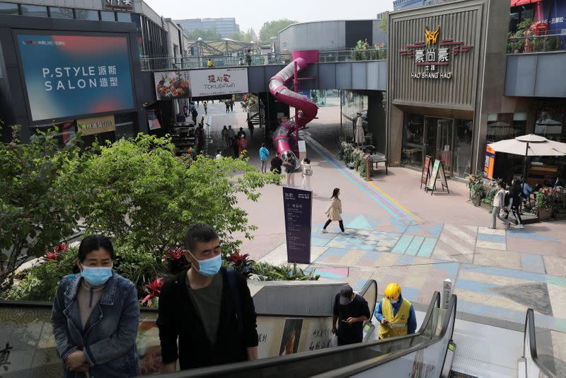 People visit a shopping complex in Beijing