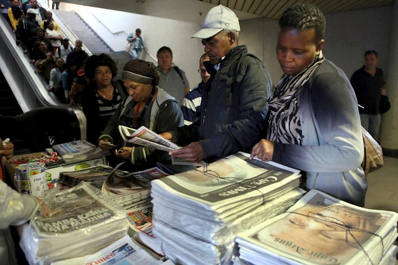 Commuters stop to buy local newspapers at Cape Town Railway Station, in Capetown, South Africa