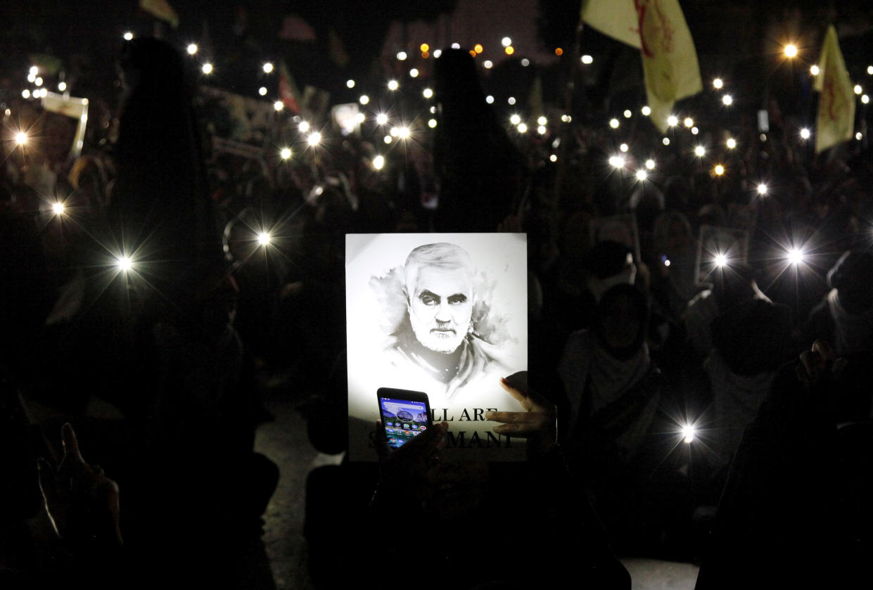 A Shiite Muslim illuminates a portrait of Iranian Revolutionary Guard Gen. Qassem Soleimani, with light from a mobile phone, during a rally to condemn his killing in Iraq by a U.S. airstrike, in Karachi, Pakistan, Sunday, Jan. 5, 2020. (Photo: Ikram Suri/AP)
