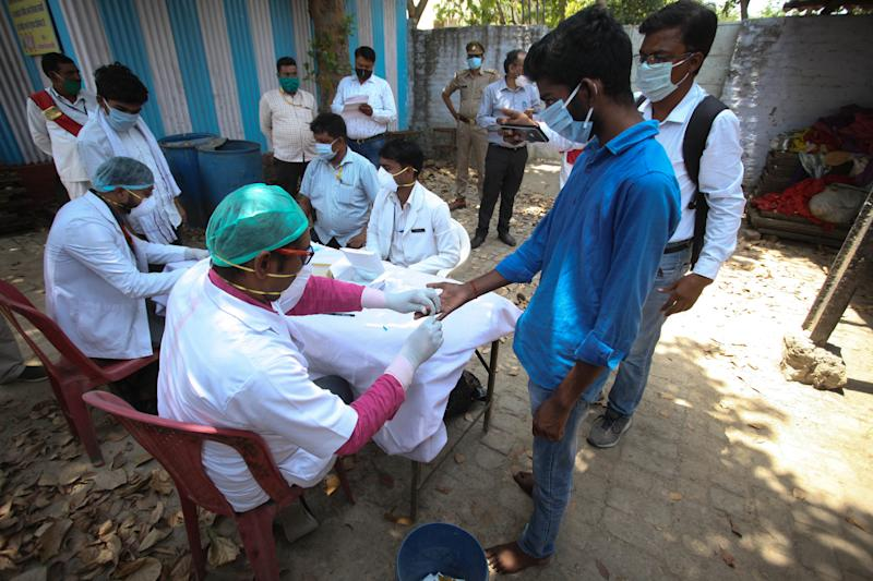 A doctor takes a blood sample of a student arrived from Kota by buses , managed by Uttar Pradesh government ,for Rapid Covid test ,in an isolation centre ,during the extended nationwide lockdown imposed by Government as a preventive measure against COVID-19 corona virus, in Allahabad, India on April 19, 2020. (Photo by Ritesh Shukla/NurPhoto via Getty Images)