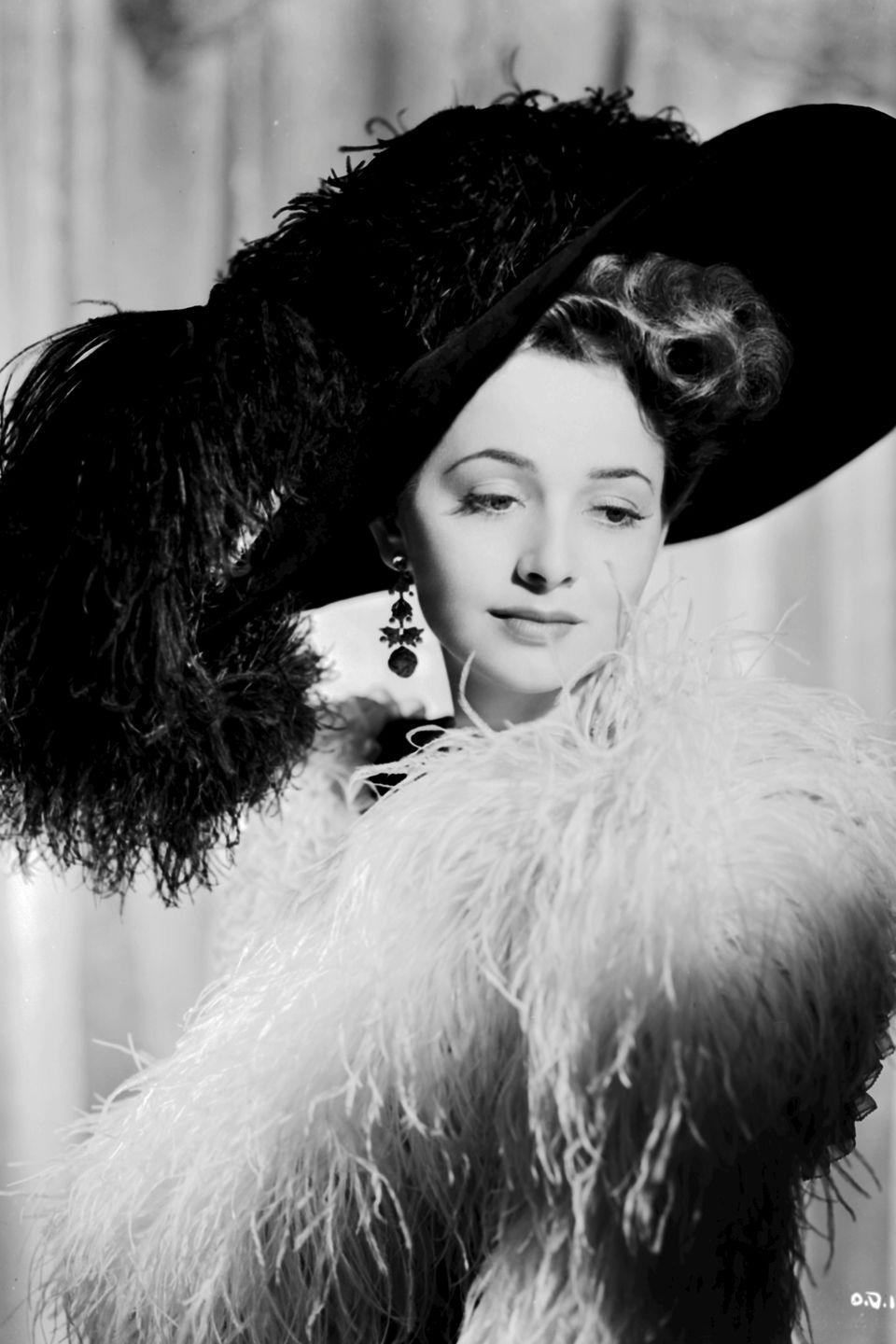 <p>Donning a feathered dress and hat for Warner Bros. Studios in a portrait shot by George Hurrell. </p>