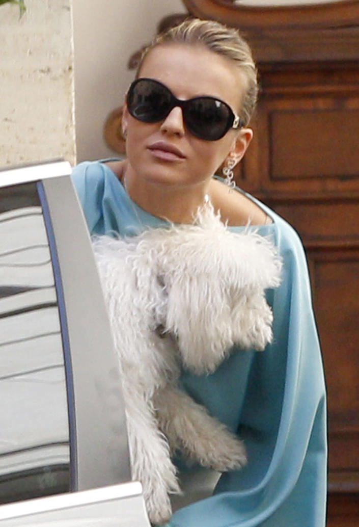 Francesca Pascale, girlfriend of Italian former Premier Silvio Berlusconi, holds her dog as she leaves his residence in Rome, Wednesday, July 31, 2013. Berlusconi is waiting in his home in Rome for the decision that will change his political fate as Italy's highest court hears arguments in the former premier's fraud conviction. Berlusconi has been convicted of tax fraud in a complex TV rights transaction for his Mediaset network, and sentenced to four-years in prison with a five-year ban on public office. This is his final appeal. (AP Photo/Riccardo De Luca)