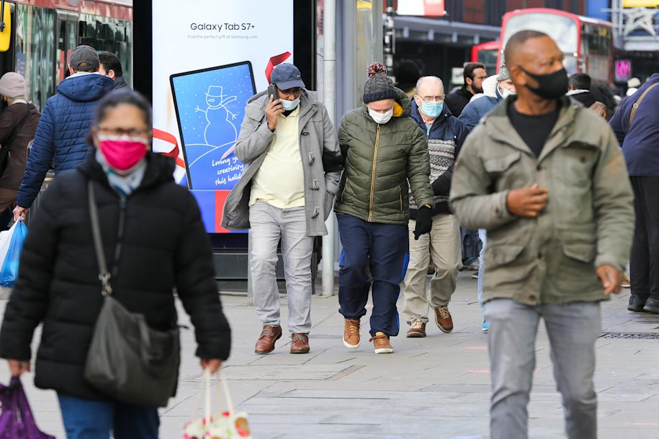 People wearing a face mask walk on the street. Prime Minister Boris Johnson announced on Saturday 19 December, that London and South East of England will move into Tier four restrictions and asked people to 'stay at home'. (Photo by Dinendra Haria / SOPA Images/Sipa USA)