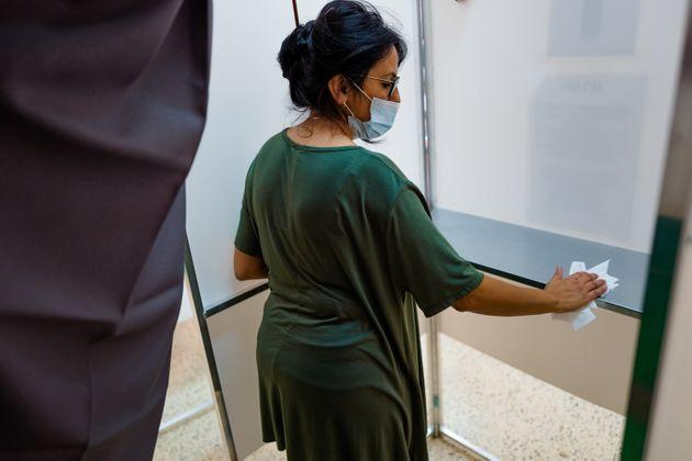 The president of the polling station of the Cesare Battisti Institute in Molfetta disinfects the polling booth on September 20 in Molfetta (Italy). On Sunday 20 September and Monday 21, almost 50 million Italians were called to the polls for the constitutional referendum to confirm the reduction in the number of parliamentarians, for the supplementary elections of the Senate, for the regional and municipal elections. In Molfetta there was a vote for the referendum (blue card) and for the Regionals (orange card). (Photo by Davide Pischettola/NurPhoto via Getty Images) (Photo: NurPhoto via Getty Images)