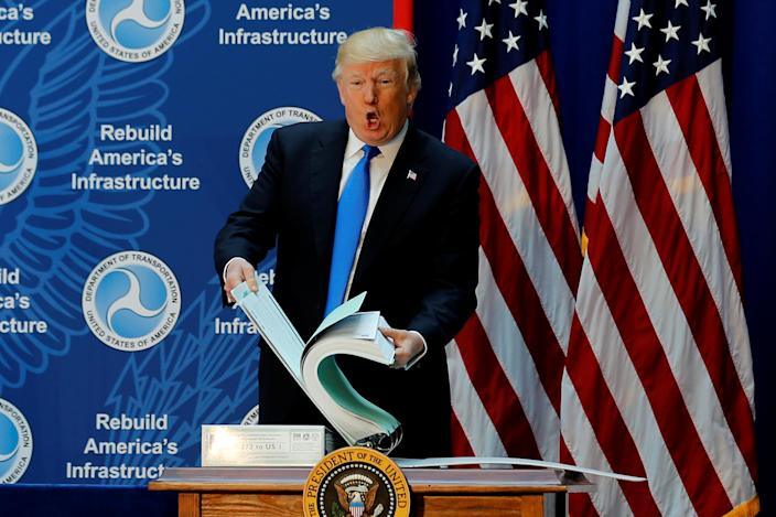 """<span class=""""s1"""">President Trump shows off a binder with highway permitting documents while discussing infrastructure improvements on June 9. (Photo: Jonathan Ernst/Reuters)</span>"""