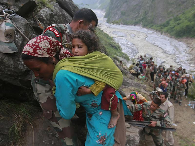 Soldiers assist a woman carrying a child on her back during rescue operations in Govindghat in the Himalayan state of Uttarakhand during the 2013 floods (REUTERS/Danish Siddiqui)