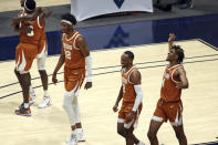 Texas forward Kai Jones (22), guard Matt Coleman III (2) and forward Greg Brown (4) celebrate after an NCAA college basketball game against West Virginia, Saturday, Jan. 9, 2021, in Morgantown, W.Va. (AP Photo/Kathleen Batten)