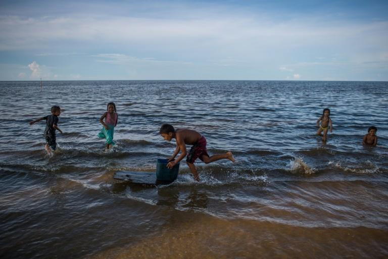 Children play on the shore of Lake Maracaibo Lake in Zulia state, Venezuela, with pieces of plastic floating on the water's surface (AFP/Federico PARRA)