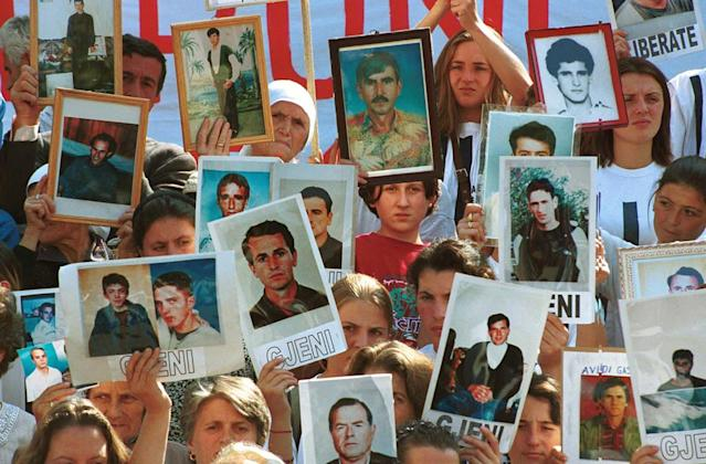 <p>Ethnic Albanians hold pictures of loved ones who are missing and believed to be held as prisoners in Serbia during a demonstration in Pristina on Sept. 20, 1999. (Photo: Jacqueline Larma/AP) </p>