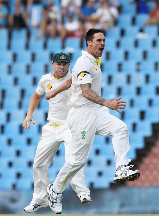 Australia's bowler Mitchell Johnson, right, with teammate David Warner, left, reacts after dismissing South Africa's batsman Faf du Plessis, for 3 runs on the second day of their their cricket Test match at Centurion Park in Pretoria, South Africa, Thursday, Feb. 13, 2014. (AP Photo/ Themba Hadebe)