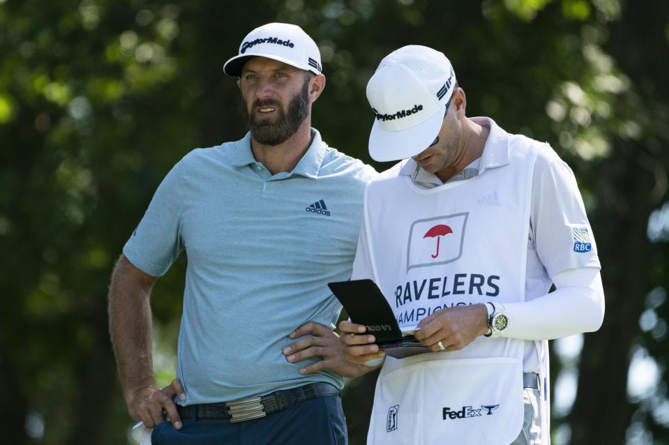 Dustin Johnson waits on the 11th tee with his caddie during the first round of the Travelers Championship golf tournament at TPC River Highlands, Thursday, June 24, 2021, in Cromwell, Conn. (AP Photo/John Minchillo)