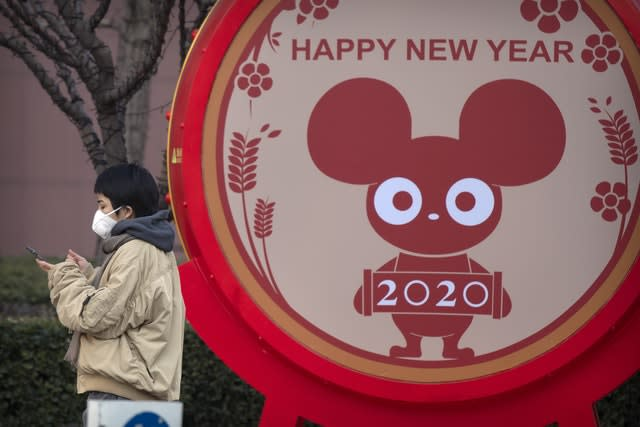 A woman wears a face mask standing near a display for the upcoming Lunar New Year, the Year of the Rat (Mark Schiefelbein/AP)